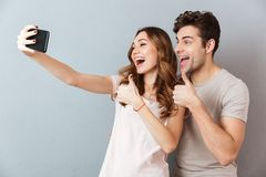 Portrait of a cheerful young couple showing thumbs up. Gesture while standing and taking a selfie over gray wall Royalty Free Stock Photo