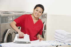 Portrait of a cheerful young employee ironing in Laundromat Royalty Free Stock Images