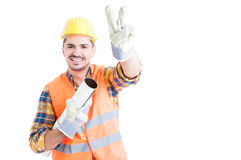 Portrait of cheerful young engineer making peace or victory gest Stock Image