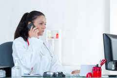 Portrait cheerful young female doctor on phone at office Royalty Free Stock Photo