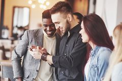 Portrait of cheerful young friends looking at smart phone while sitting in cafe. Mixed race people in restaurant using. Mobile phone stock image