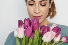 Portrait of a cheerful young girl holding pink tulips bouquet isolated over white background.  royalty free stock photos