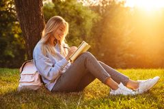 Portrait of a cheerful young girl. Sitting on a grass at the park, reading a book, taking notes Royalty Free Stock Photos