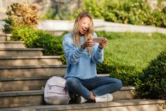 Portrait of a cheerful young girl student with backpack. Playing games on mobile phone while sitting outdoors Stock Photos