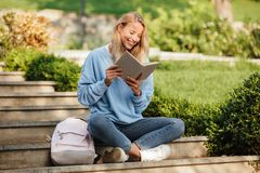 Portrait of a cheerful young girl student with backpack. Sitting on steps outdoors, reading book Royalty Free Stock Photo