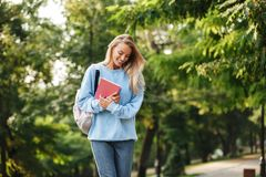 Portrait of a cheerful young girl student with backpack. And textbook walking at the park Royalty Free Stock Images
