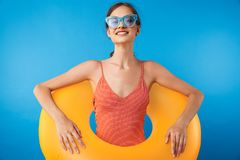 Portrait of a cheerful young girl in swimsuit. Wearing sunglasses holding inflatable ring over blue background royalty free stock image