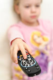 Portrait of cheerful young girl uses remote control to change television channels Stock Images