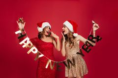 Portrait of a cheerful young girls dressed in shiny dresses. Holding happy new year ribbon while standing and looking at each other over red background Royalty Free Stock Photos