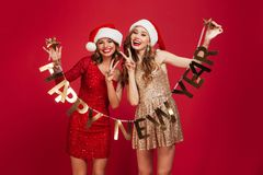 Portrait of a cheerful young girls dressed in shiny dresses. Holding happy new year ribbon while standing and showing peace gesture over sparkly golden Stock Photo