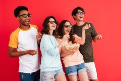 Portrait of a cheerful young group of multiracial friends. In 3d glasses having fun while standing together with popcorn and watching a movie isolated over red stock image