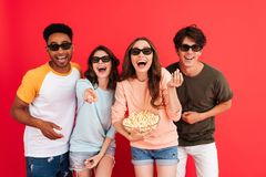 Portrait of a cheerful young group of multiracial friends. In 3d glasses having fun while standing together with popcorn and pointing isolated over red stock image