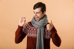 Portrait of a cheerful young man dressed in sweater. And scarf isolated over beige background, showing thermometer, showing thumbs up stock photo