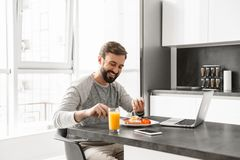 Portrait of a cheerful young man having breakfast Royalty Free Stock Images