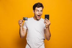 Portrait of a cheerful young man holding mobile phone. And showing credit card isolated over yellow background royalty free stock photo