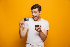Portrait of a cheerful young man holding mobile phone. And showing credit card isolated over yellow background stock photos