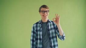Portrait of cheerful young man showing OK gesture and smiling looking at camera stock video