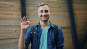 Portrait of cheerful man showing OK gesture smiling looking at camera outoors. Portrait of cheerful young man showing OK gesture and smiling looking at camera stock video footage
