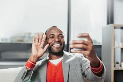 Glad male making video call on cellphone. Portrait of cheerful young man sitting with comfort inside, holding device and talking in internet Royalty Free Stock Image