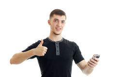 Portrait of a cheerful young man in a t-shirt that shows class and holds in his hand shaving Clipper Stock Image