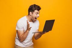 Portrait of a cheerful young man using laptop computer. Isolated over yellow background stock images