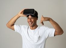 Portrait of cheerful young man wearing Virtual Reality goggles for first time smiling at camera royalty free stock photos