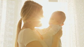 Portrait of cheerful young mother with her baby boy in sun rays in front of big window