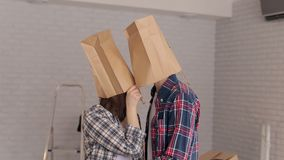 Portrait of happy young people who put on their heads paper bags, housewarming. Portrait of cheerful young people who put on their heads paper bags stock video footage