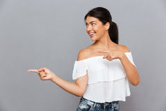Portrait of a cheerful young smiling woman pointing finger away Stock Photos
