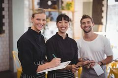 Portrait of cheerful young wait staff holding digital tablet with notepad and clipboard. At coffee shop Stock Image