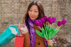 Portrait of cheerful young woman with beautiful purple tulips. royalty free stock photography