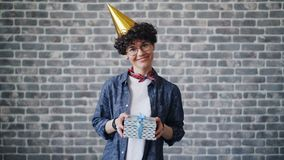 Portrait of cheerful young woman in bright party hat holding gift box smiling stock video footage