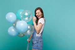 Portrait of cheerful young woman in denim clothes blinking, celebrating and holding colorful air balloons isolated on. Blue turquoise wall background. Birthday royalty free stock photos