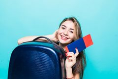 Portrait of a cheerful young woman dressed in summer clothes holding passport with flying tickets while standing with a suitcase royalty free stock photography