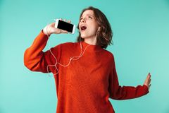 Portrait of a cheerful young woman dressed in sweater. Listening to music in earphones isolated over blue background Royalty Free Stock Image