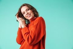 Portrait of a cheerful young woman dressed in sweater. Looking at camera isolated over blue background Royalty Free Stock Photos