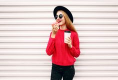 Portrait cheerful young woman eating sweet donut and holding coffee cup on city street white wall. Background stock photography