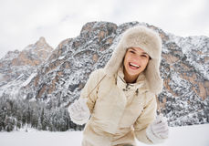 Portrait of cheerful young woman in fur hat in winter outdoors. Magical mix of winter season and mountain landscape create the perfect mood. Portrait of cheerful Stock Images