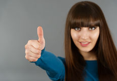 Portrait Of Cheerful Young Woman Gesturing Okay Sign on a gray Royalty Free Stock Photo