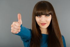 Portrait Of Cheerful Young Woman Gesturing Okay Sign on a gray Stock Photography