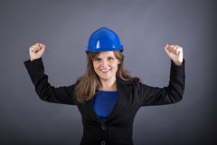 Portrait of cheerful young woman with hardhat  with arms raised Royalty Free Stock Photography