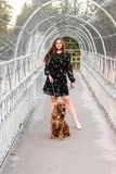 Portrait of cheerful young woman with her dog on the bridge in park. Friendship, pet and human. royalty free stock photos