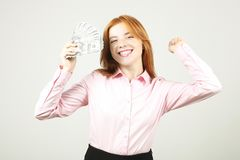 Portrait of cheerful young woman holding bunch of one hundred dollar bills and celebrating in winning pose, hands up raised fist. stock photography