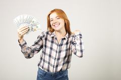Attractive young businesswoman posing with bunch of USD cash in hands showing positive emotions and happy facial expression. Portrait of cheerful young woman stock images