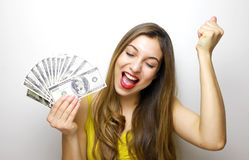Portrait of a cheerful young woman holding money banknotes and celebrating isolated over white background stock photography