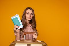 Portrait of cheerful young woman holding passport with tickets sitting near the suitcase stock photo