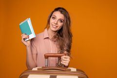 Portrait of cheerful young woman holding passport with tickets sitting near the suitcase royalty free stock photo