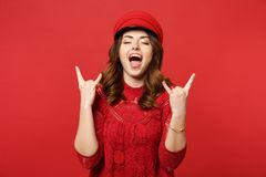 Portrait of cheerful young woman in lace dress cap keeping eyes closed depicting heavy metal rock sign isolated on stock image