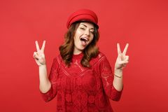 Portrait of cheerful young woman in lace dress cap keeping mouth open, showing victory sign isolated on bright red royalty free stock photos
