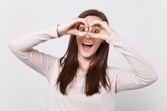 Portrait of cheerful young woman in light clothes holding hands near eyes, imitating glasses or binoculars on. White background. People sincere emotions royalty free stock photos